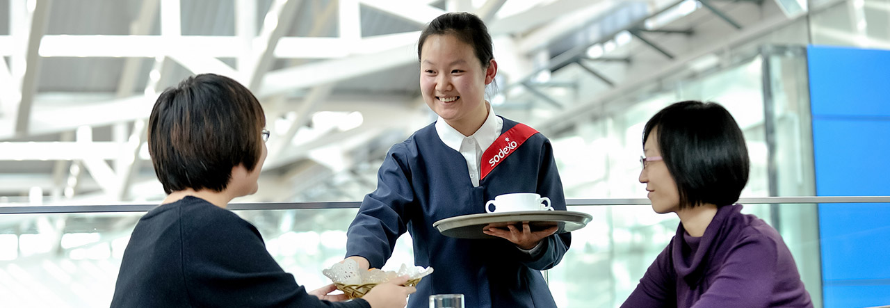 Woman serving two customers